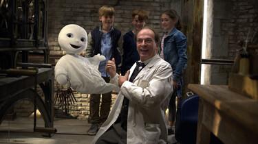 Szenenbild: Das kleine Gespenst mit einem Mann in einem weißen Kittel. Im Hintergrund stehen drei Kinder