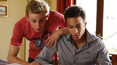 Szenenbild: Damien beugt sich über Thomas, der an einem Schreibtisch sitzt