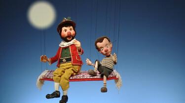 Szenenbild: Zwei Marionetten auf einer Schaukel, im Hintergrund der Vollmond
