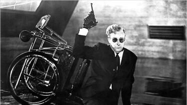 Szenenbild: Peter Sellers als Dr. Seltsam mit einer Waffe vor seinem umgekippten Rollstuhl sitzend