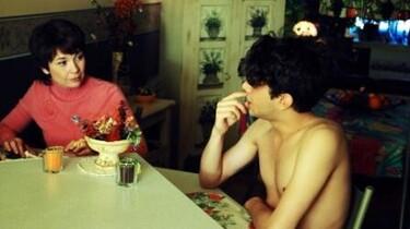 Szenenbild: Ein Mann sitzt ohne Kleidung mit einer Dame am Tisch
