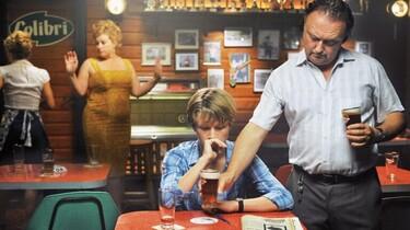 Szenenbild: In einer Kneipe: Einem sehr jungen Mann wird von einem älteren ein Bier hingestellt