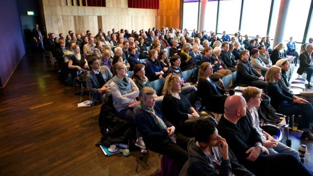 Blick auf die gefüllten Reihen im großen Saal des KOMED Köln während einer Podiumsdiskussion