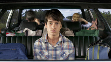 Szenenbild: Der Protagonist mit gelangweilten Blick im Fond eines Autos