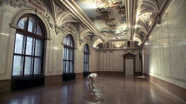 Szenenbild: Ein Mann in einem leeren Museums-Salon. Mit einem Hammer ist er am Boden beschäftigt