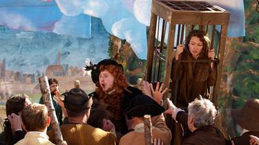 Szenenbild: eine Frau in einem Holzkäfig auf einem mittelalterlichen Markt, daneben ein Marktschreier und davor eine Menschenmenge