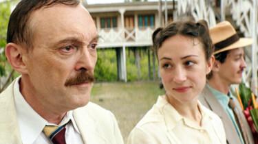 Szenenbild: Josef Hader als Stefan Zweig links im Bildvordergrund, dahinter seine Frau Lotte. Beide tragen weiße Kleidung, im Hintergrund Palmen, grün und ein weißes Haus sowie ein weiterer Mann mit Strohhut