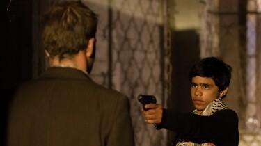 """Szenenbild: Der 12-jährige Fahed bedroht einen Mann mit einer Pistole"""""""
