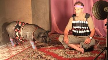 Szenenbild: Mann und Schwein mit Sprengstoffgürtel auf einem Teppich im Scheinwerferlicht