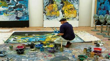 Szenenbild: Umringt von unzähligen Farbtöpfen, Pinseln und Wischtüchern malt Georg Baselitz an einem großformatigen Gemälde