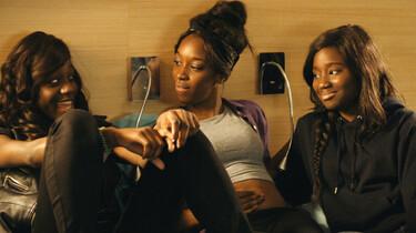 Szenenbild: drei der Mädchen sitzen vor einer Wand in einem Hotelzimmer und quatschen