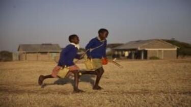 Szenenbild: Zwei afrikanische Kinder in Schuluniform rennen über Steppengras, im Hintergrund Gebäude