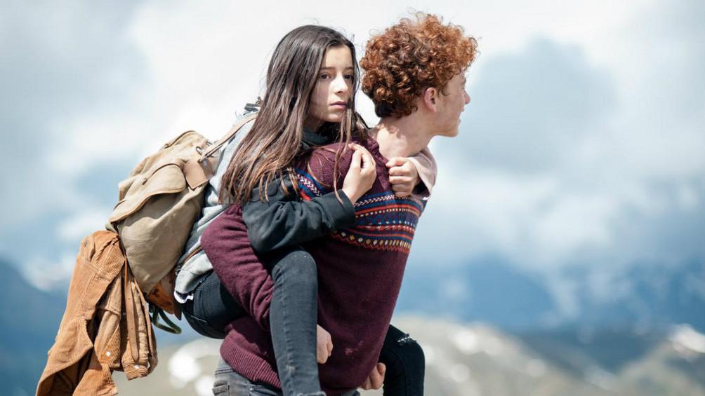 Szenenbild: Bart trägt Amelie auf dem Rücken, im Hintergrund Alpenpanorama