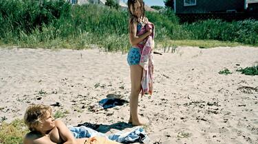 Szenenbild: am Strand: Ein Mädchen im  Badezug schaut auf einen am Boden liegenden Jungen