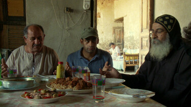 Szenenbild: Drei Männer sitzen beim Essen an einem Tisch
