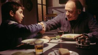 Szenenbild: Mann und Junge am Tisch sitzend geben sich die Hand