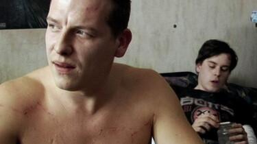 Szenenbild: Mann mit nacktem Oberkörper im Bildvordergrund, im Hintergrund junger Mann  auf Sofa