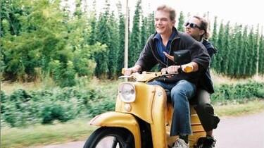 Szenenbild: Annika und ein junger Mann auf einem gelben Motorroller