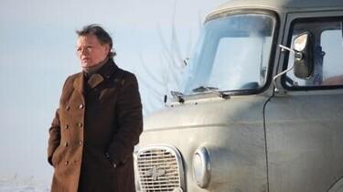 Szenenbild: die alte Nachbarin lehnt an dem betagten Transporter