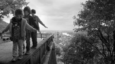 Die drei geschwister balancieren auf einem Geländer.