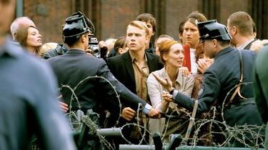 Szenenbild: Menschenmenge hinter Stacheldrahtzaun, Polizisten sind auf der anderen Seite
