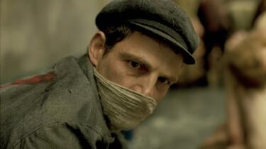 Szenenbild: Porträt von Saul Ausländer mit Mütze und einem Tuch vor dem Mund.