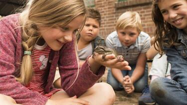 Szenenbild: Hauptprotagonistin Sita inmitten einer Kindergruppe, auf ihrer ausgestreckten Hand sitzt ein Frosch