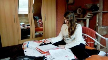 Szenenbild: Das 14-jährige Mädchen macht Hausaufgaben