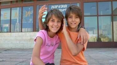 Szenenbild: Zwei Kinder sitzen vor einem Gebäude und lachen