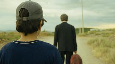 Szenenbild: Nori mit Kopfverband von hinten zu sehen. Er blickt seinem Vater nach, der auf einer unbefestigten Straße davongeht.
