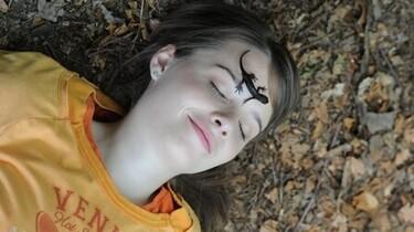 Szenenbild: Ein Mädchen liegt auf dem Boden. AUf ihrem Gesicht sitzt eine Eidechse