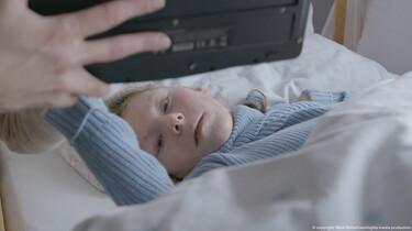 Ein Mädchen liegt im Bett mit weißer Bettwäsche und guckt mit leichtem Silberblick in die Kamera.