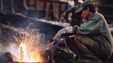 Szenenbild: Ein junger Mann erzeugt durchs Arbeiten ein Feuer