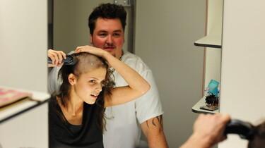 Sophie rasiert sich vor dem Spiegel die Harre vom Kopf ab.