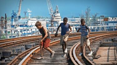 Szenenbild: Chala und zwei Freunde springen über die Gleise.
