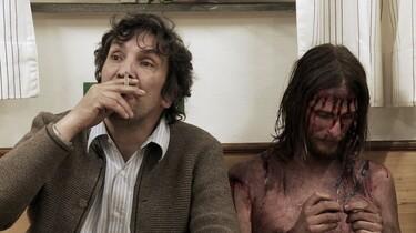 Szenenbild: Ein Mann mit Zigarette neben einem Jesusdarsteller