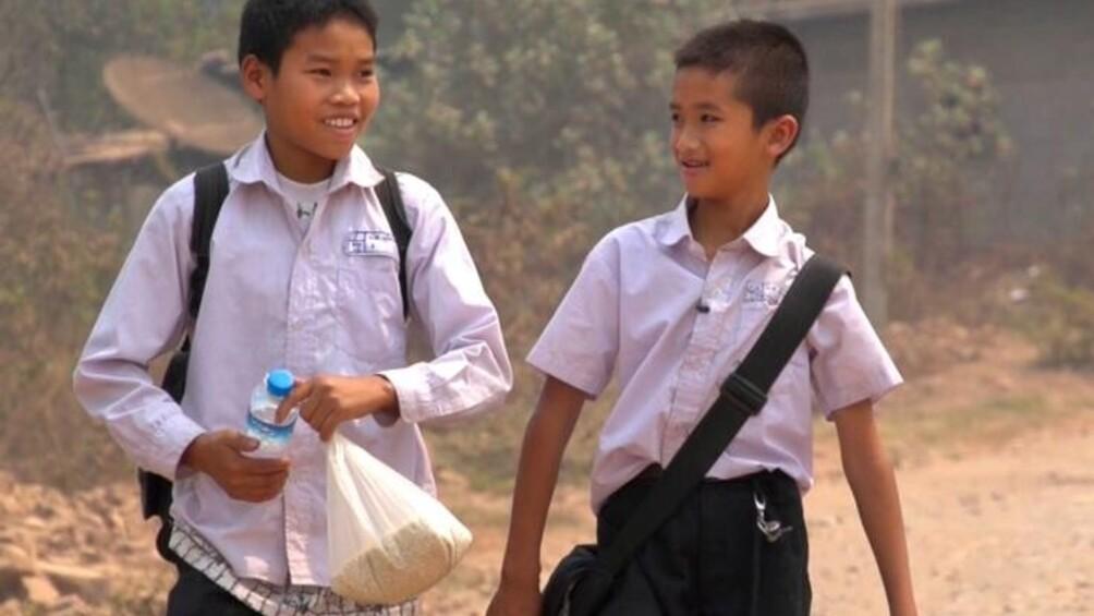 Zwei asiatische Jungen in Schuluniform gehen auf staubiger Straße