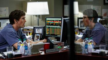 Szenenbild: Hedgefond Manager am Schreibtisch vor Bildschirm, spiegelt sich in Scheibe