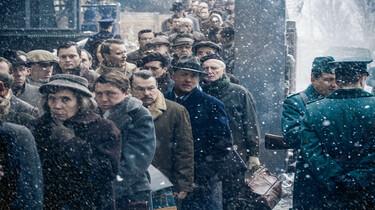 Szenenbild: Eine große Anzahl wartender Menschen in einer Warteschlange, darunter Tom Hanks