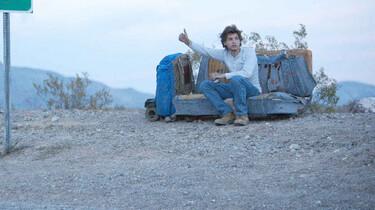 Szenenbild: Ein junger Mann sitzt verlassen auf einem Sofa in freier Wildnis