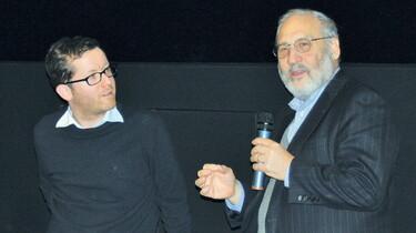 Szenenbild: Zwei Männder vor dunklem Hintergrund, einer mit Mikrofon in der Hand