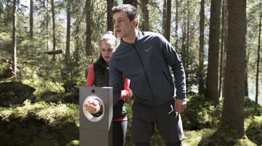 Szenenbild: Zach und Nadesh im Wald, sie checken ihre Armbänder in ein Gerät ein