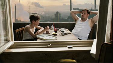 Szenenbild: Vater und Sohn am Frühstückstisch auf dem Balkon, im Hintergrund rauchende Schlote