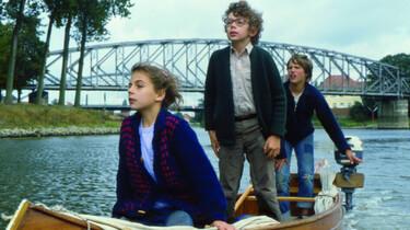 Drei Kinder fahren auf einem Boot den Fluss entlang.