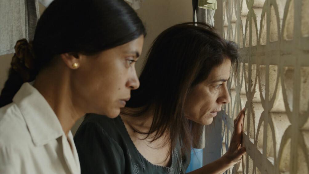Szenenbild: Zwei Frauen schauen von einem Balkon, der mit einem Steingitter abgegrenzt ist. Wir sind mit Ihnen auf dem Balkkon