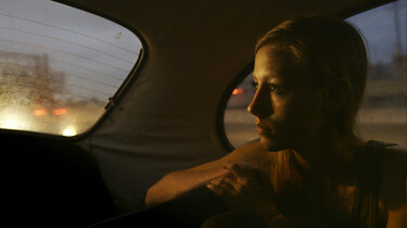 Szenenbild: Layla, auf der Rückband eines Autos sitzend, schaut nach hinten aus dem Fenster, draußen Dämmerlicht