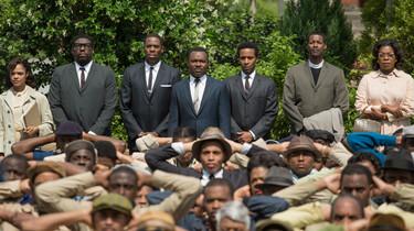 Szenenbild: Gruppe von Demonstranten, die vorderen sitzen, eine hintere Reihe stehend