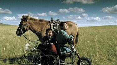 Szenenbild: zwei Jungen auf einem Fahrrad vor einem Pferd