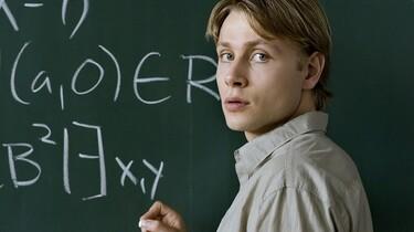 Szenenbild: Ein junger Mann vor einer grünen Tafel
