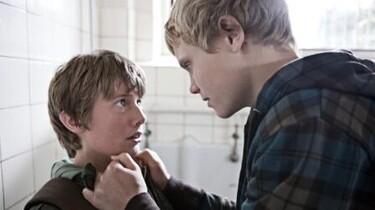 Szenenbild: Ein blonder Junge packt einen kleineren JUngen am Kragen
